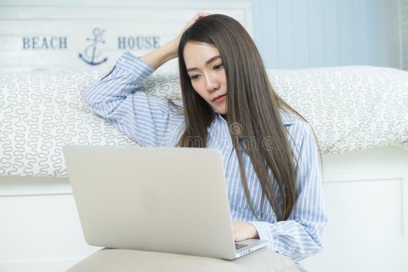 Aziatische jonge vrouw die laptop computer in haar slaapkamer met behulp van stock foto's