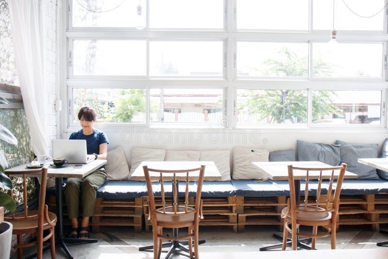 Aziatische jonge vrouw die reisinformatie via laptop zoeken comput royalty-vrije stock afbeelding