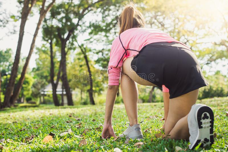 Aziatische jonge vrouw op teken voor joggingoefening klaar te plaatsen om haar lichaam op glas in warme lichte ochtend op te bouw stock foto