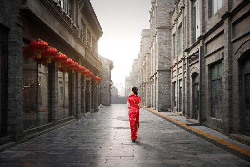 Aziatische jonge vrouw in oude traditionele Chinese kleding in Hutong v stock foto