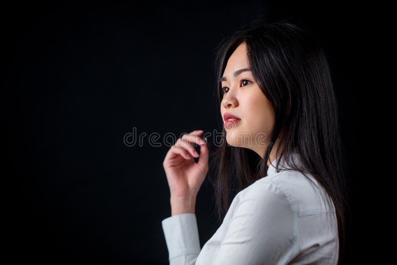 Aziatische jonge vrouw in wit over zwarte achtergrond Zwarte en whit royalty-vrije stock afbeelding
