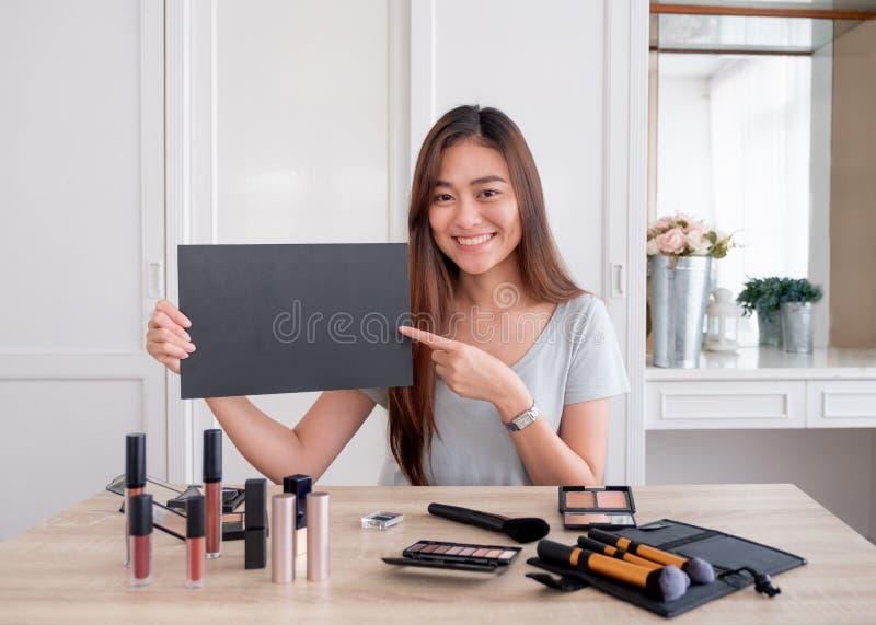 Aziatische jonge vrouwelijke de giftventilator van het bloggerweggevertje na kanaal terwijl thuis online het registreren van vlog stock foto's