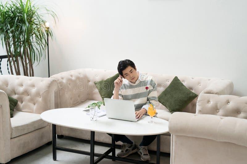 Aziatische jonge zakenman die aan zijn laptop in een koffiewinkel werken stock foto's
