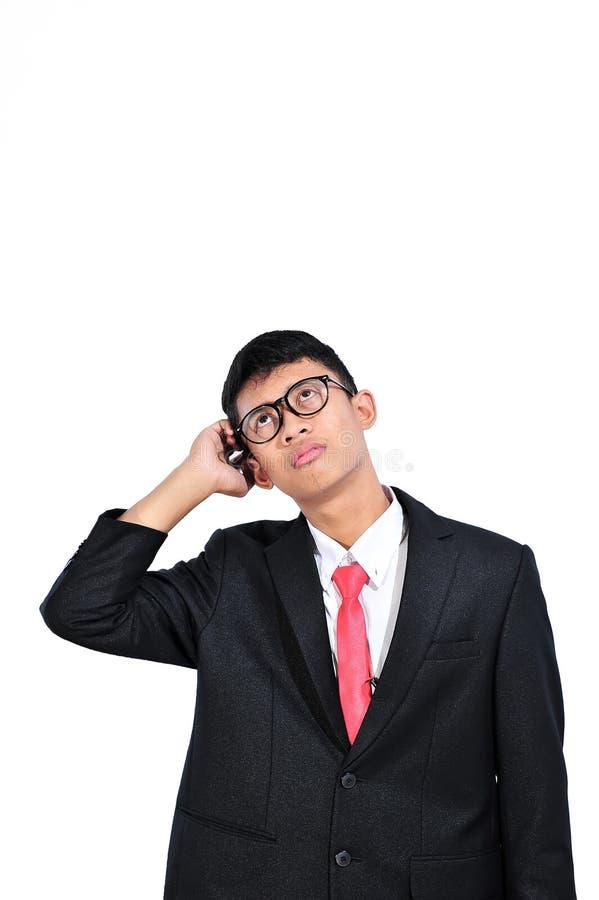 Aziatische jonge zakenman die over vraag, hand over hoofd, peinzende uitdrukking denken Verwarring met nadenkend gezicht Twijfelc stock foto's