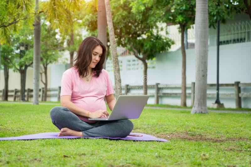 Aziatische jonge zwangere vrouwenzitting op gras die laptop met behulp van stock afbeelding