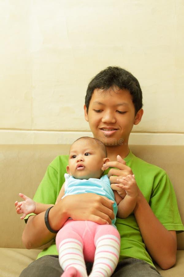 Aziatische jongen babysit een baby royalty-vrije stock foto's