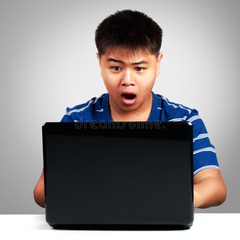 Aziatische jongen bij de verraste computer stock afbeelding