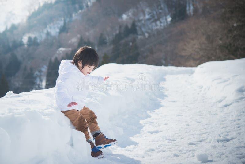 Aziatische jongen in de winterkleren met sneeuwachtergrond royalty-vrije stock afbeelding