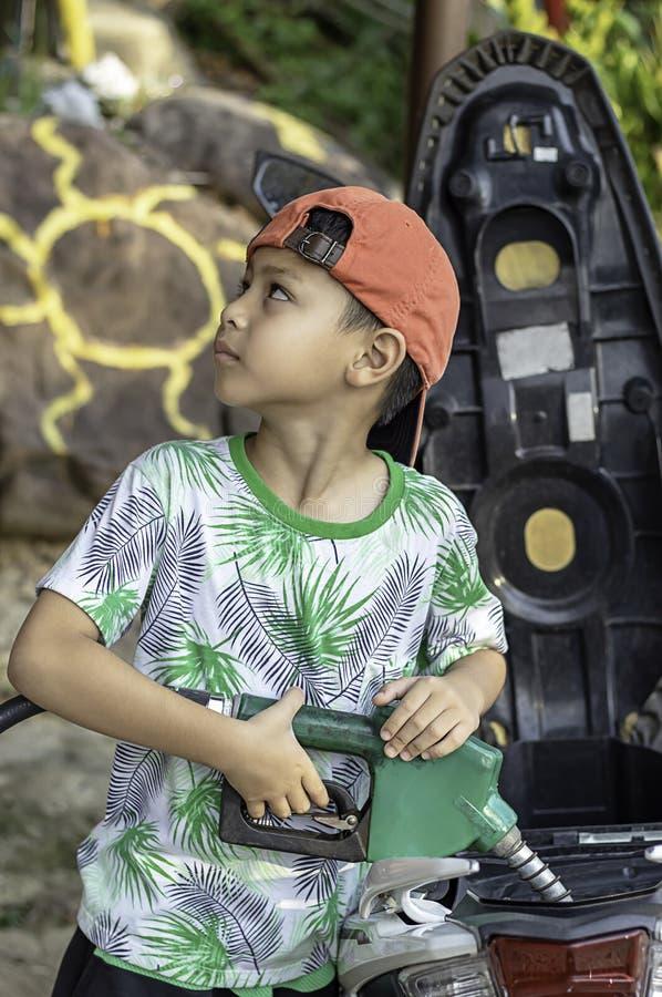 Aziatische jongen die brandstof opvullen in de motor royalty-vrije stock afbeeldingen