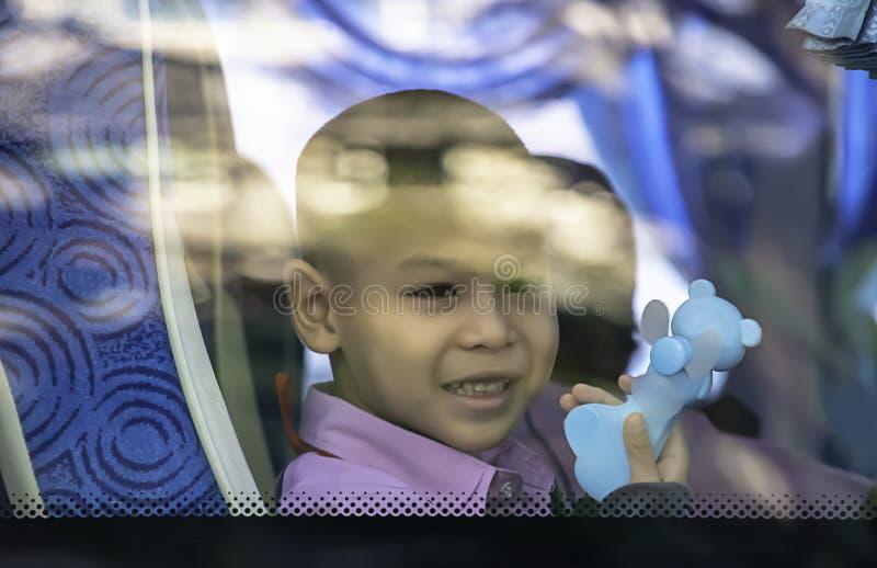 Aziatische jongen die de draagbare kleine ventilatorzitting op een schoolbus houdt royalty-vrije stock afbeeldingen