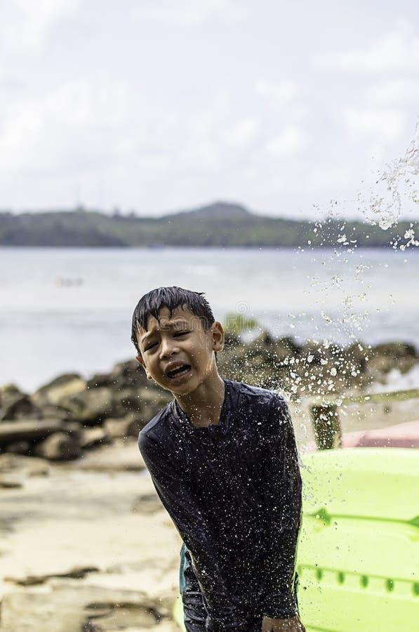 Aziatische jongen die een zwempak en douche Achtergrondoverzees dragen stock afbeeldingen