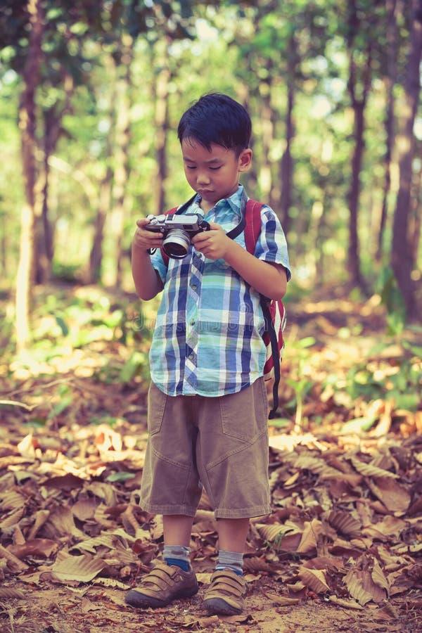 Aziatische jongen die foto's in digitale camera controleren Uitstekend beeldvarkenskot stock afbeelding