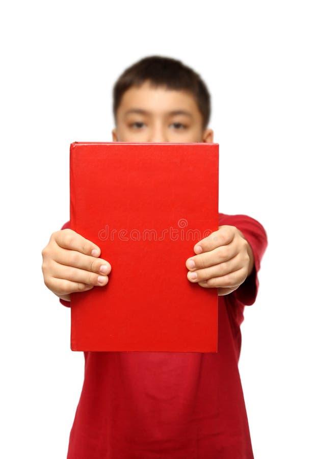 Aziatische jongen die groot rood boek toont stock fotografie