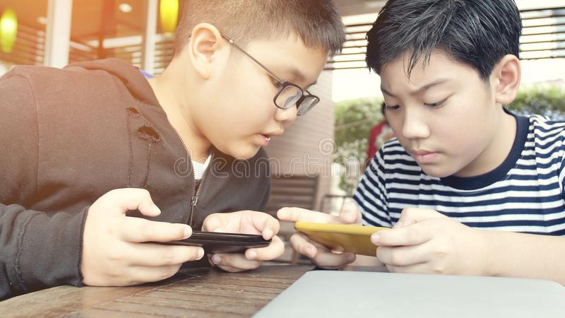 Aziatische jongen die mobiel spel op slimme telefoon samen spelen royalty-vrije stock fotografie