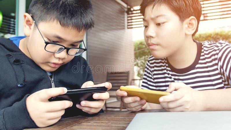 Aziatische jongen die mobiel spel op slimme telefoon samen spelen stock foto