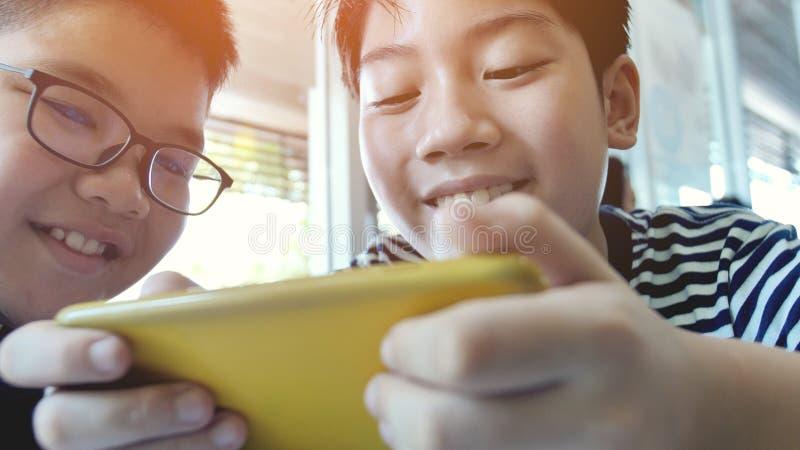 Aziatische jongen die mobiel spel op slimme telefoon samen spelen royalty-vrije stock foto's