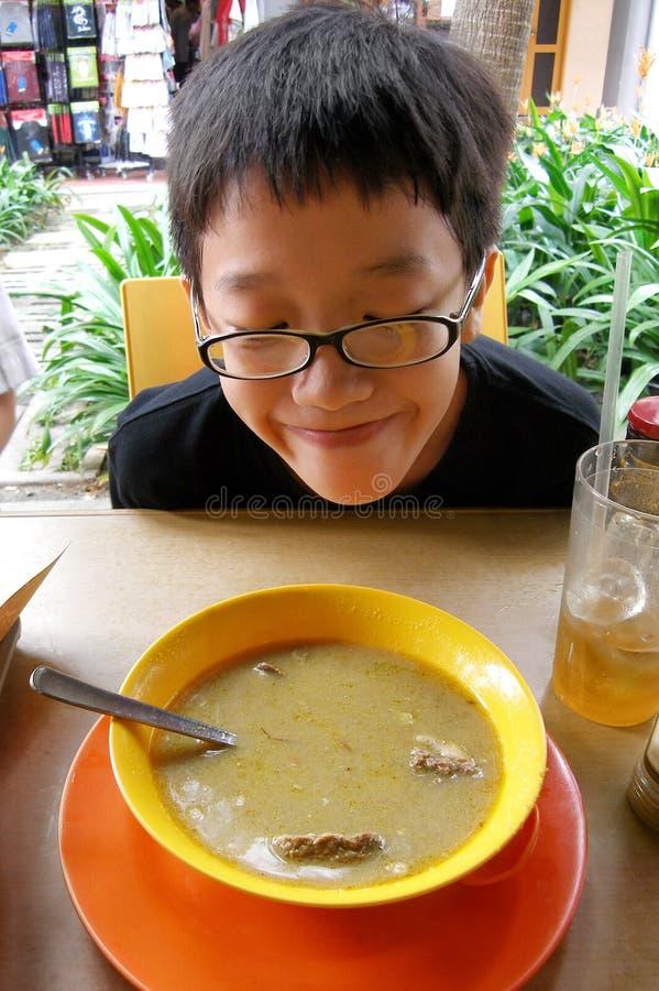 Aziatische jongen die straatvoedsel proberen stock afbeelding