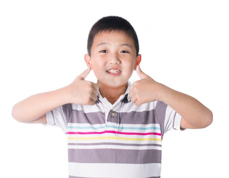 Aziatische jongen die u duimen over witte geïsoleerde achtergrond opgeven, stock foto