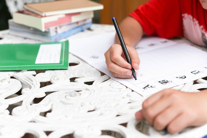 Aziatische jongen die zijn thuiswerk doen stock afbeeldingen