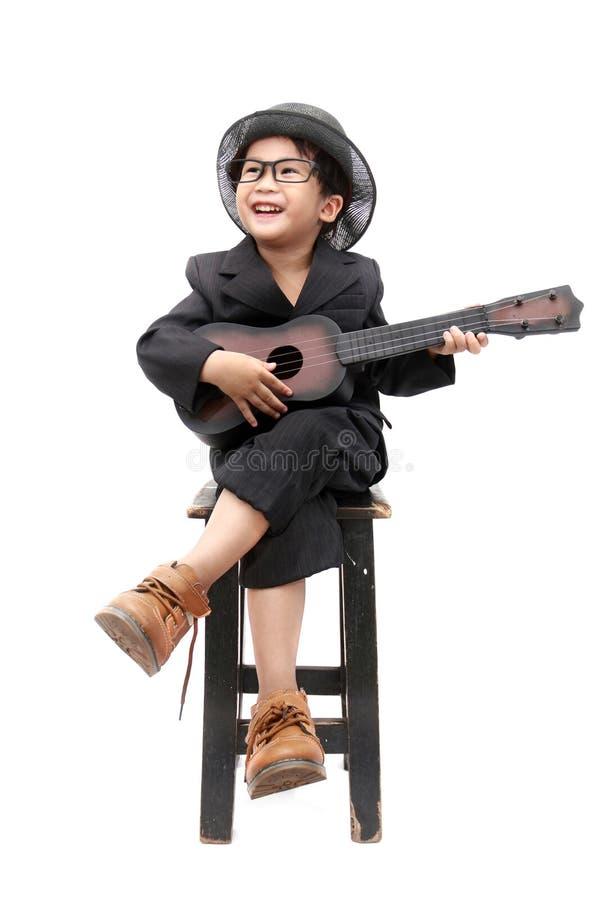Aziatische jongen het spelen gitaar op geïsoleerde witte achtergrond stock fotografie