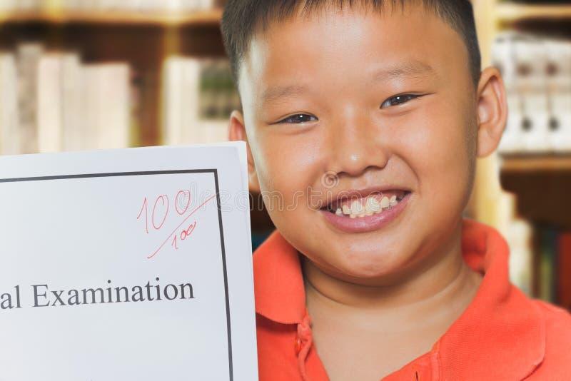 Aziatische jongen met de volledige bladen van het scoreonderzoek stock afbeeldingen
