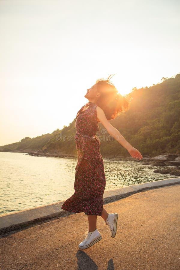 Aziatische jongere vrouw die en medio lucht springen drijven tegen beautif stock foto