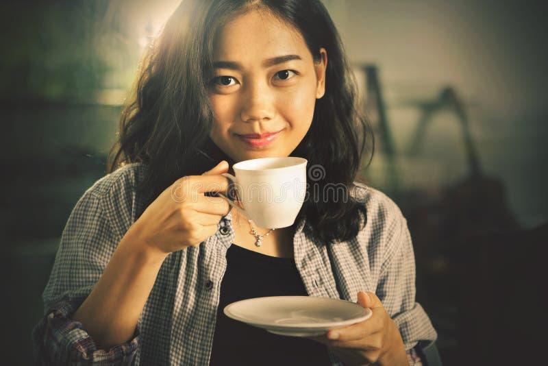 Aziatische jongere vrouw die hete koffie in witte kop drinken royalty-vrije stock fotografie