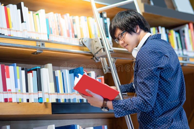 Aziatische kerel die boek kiezen van boekenrek in bibliotheek stock foto's