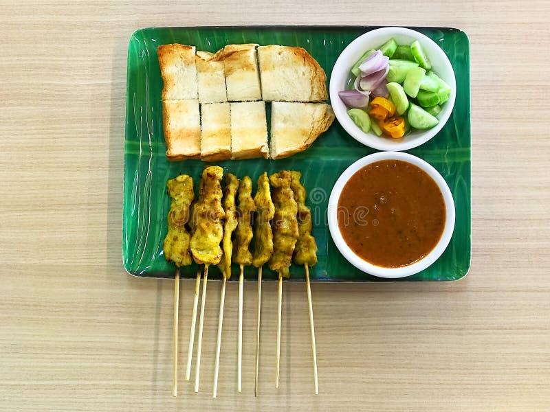 Aziatische Keuken, Varken Satay of Moo Satay met toost op groene schotel en houten lijst stock foto
