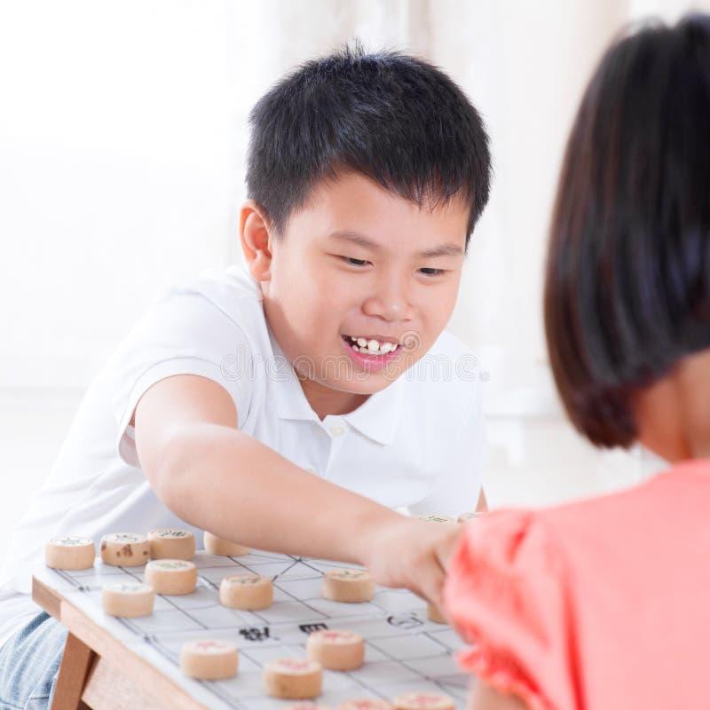 Aziatische kinderen die Chinees schaak spelen royalty-vrije stock afbeeldingen
