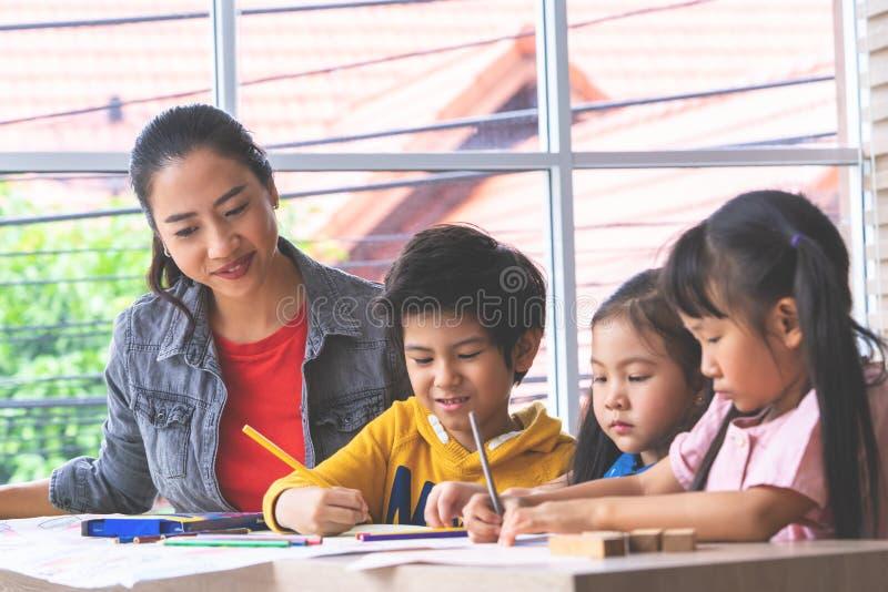 Aziatische kinderen die in Kunstklasse schilderen met leraar, voor creati stock foto's