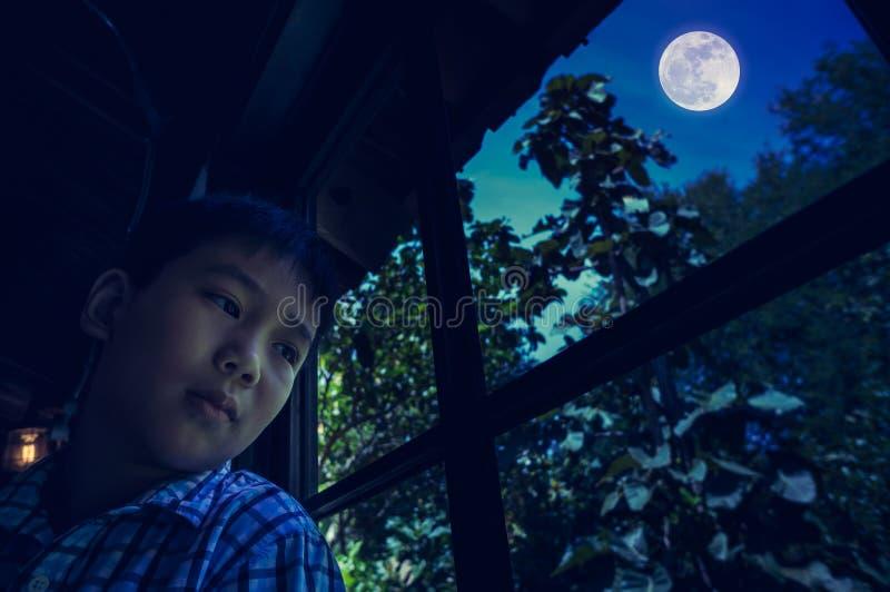 Aziatische kindzitting dichtbij venster en het kijken opzij terwijl het voelen royalty-vrije stock foto's