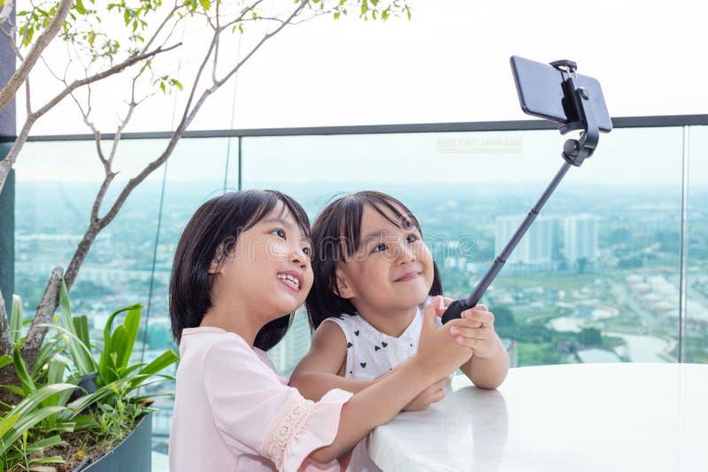 Aziatische Kleine Chinese Zusters die selfie met smartphone op selfiestok nemen stock foto