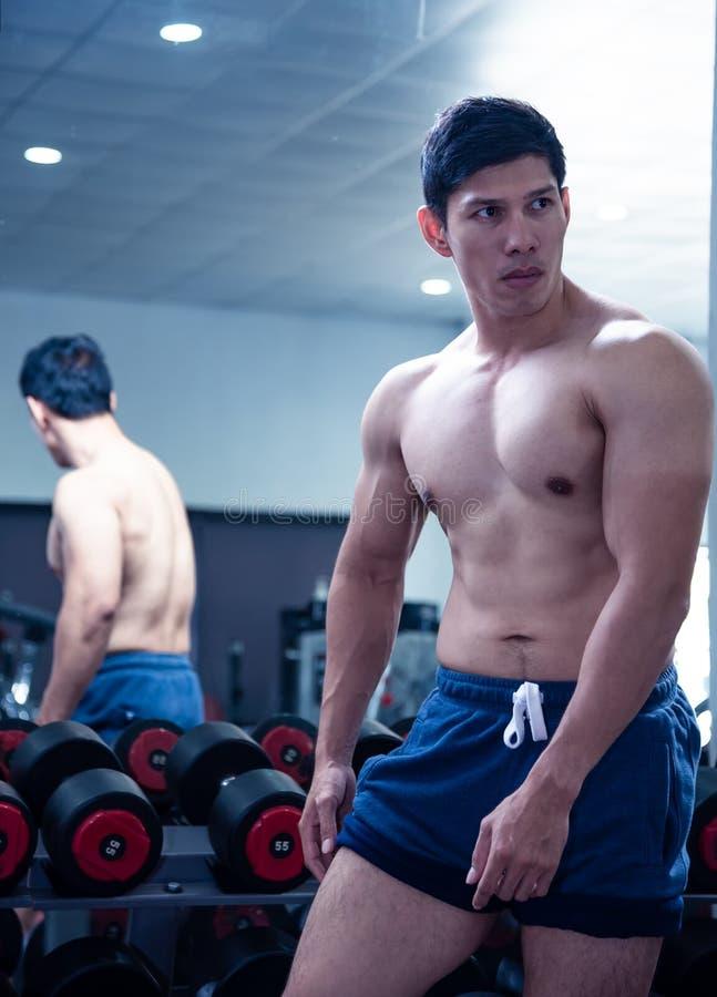 Aziatische knappe jonge spier Aziatische mens die bodybuilder voor een glas in de gymnastiek uitoefenen De kerelverbuiging leidt  royalty-vrije stock foto