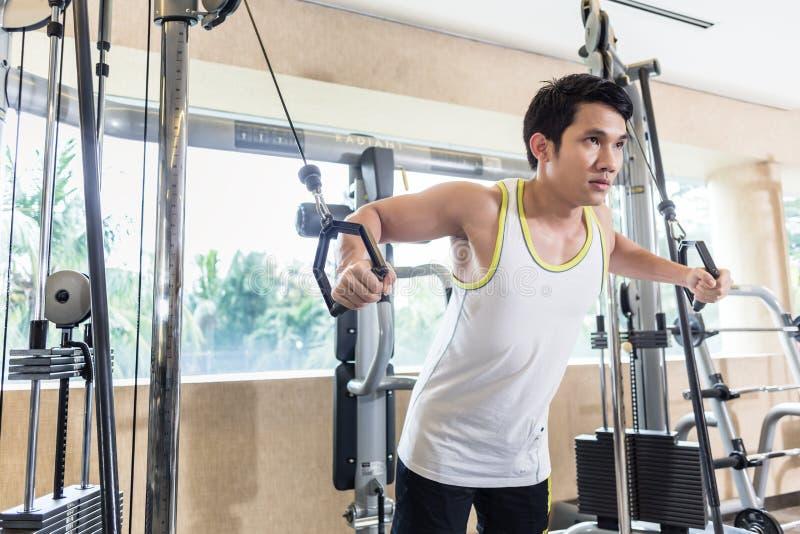 Aziatische knappe mens die kabeloversteekplaats voor borstspieren uitoefenen stock foto