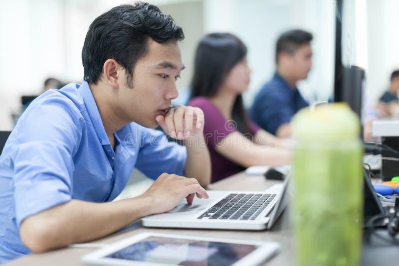 Aziatische Laptop van Zakenmansitting at desk Werkende Computerzaken royalty-vrije stock afbeeldingen