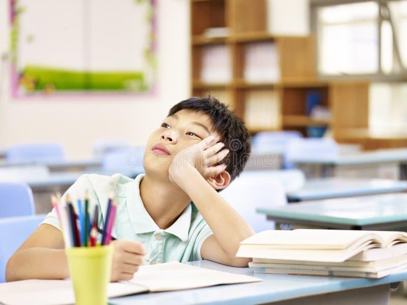 Aziatische leerling die in klaslokaal denken royalty-vrije stock fotografie