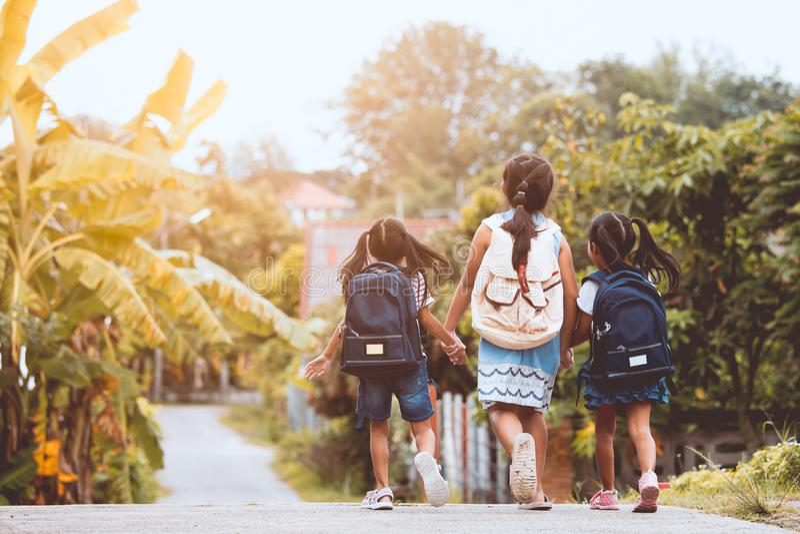 Aziatische leerlingsjonge geitjes met rugzak die naar school gaan royalty-vrije stock fotografie