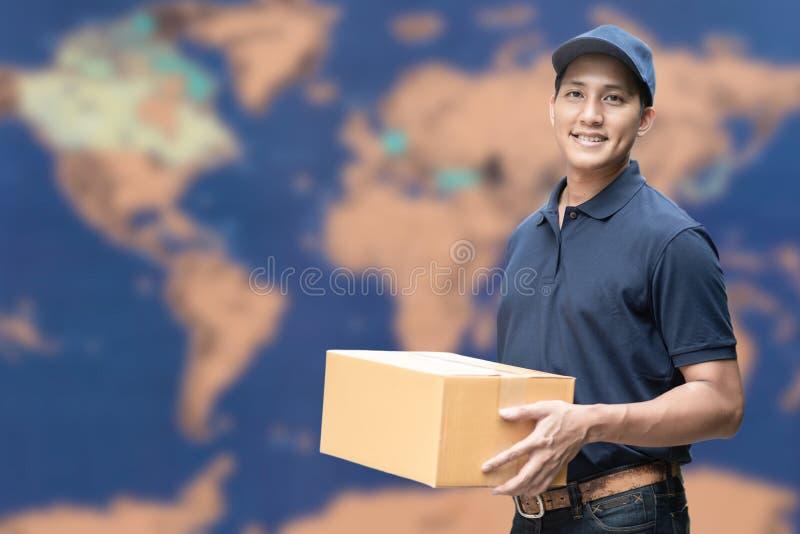 Aziatische leveringsmens die een kartondoos met globale kaart op achtergrond houden stock foto