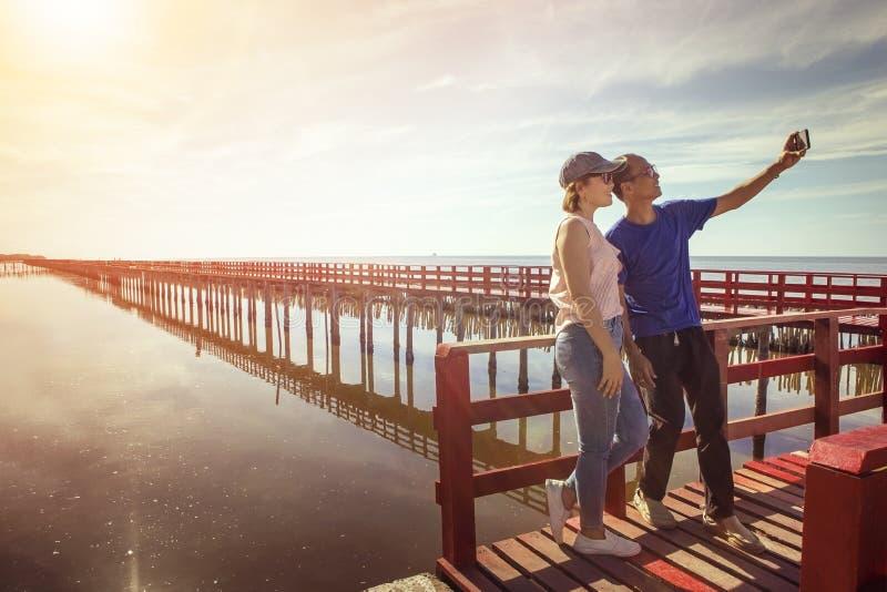 Aziatische man en vrouw die een foto op rode houten brug nemen tegen su stock foto