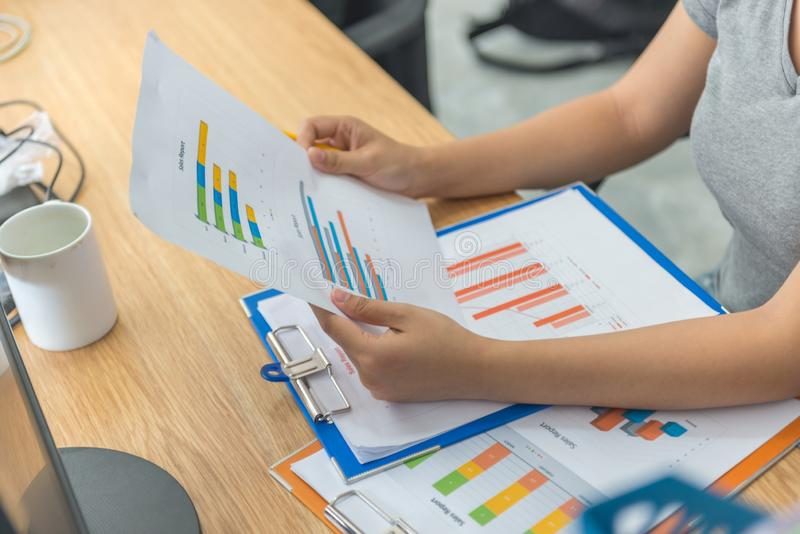 Aziatische manager die financiële verkooprapporten in haar bedrijfsbureau controleren royalty-vrije stock fotografie
