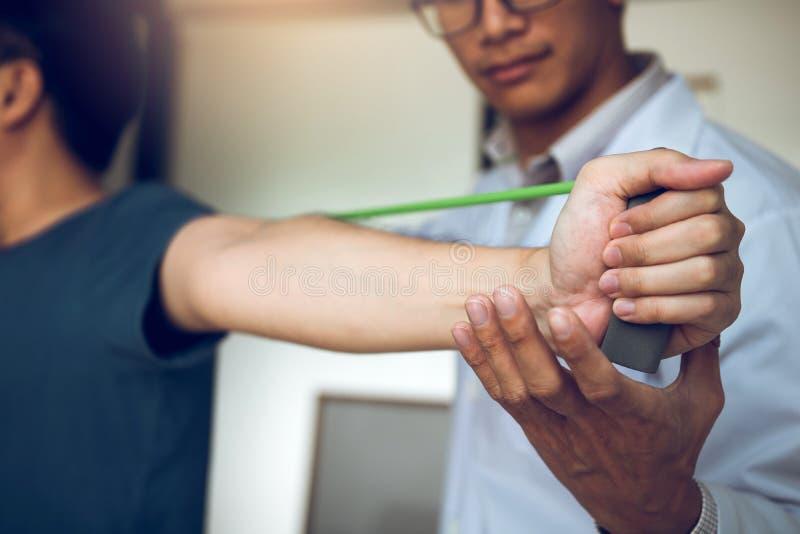Aziatische mannelijke fysiotherapeutafdaling die en de handen van pati?nten met geduldige het doen uitrekkende oefening werken he royalty-vrije stock afbeeldingen