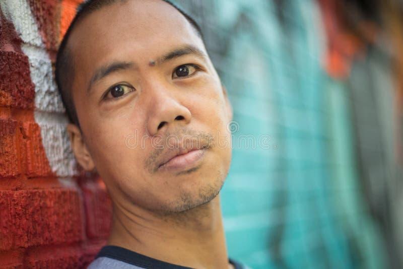 Aziatische mannelijke status tegen graffitimuur stock afbeeldingen