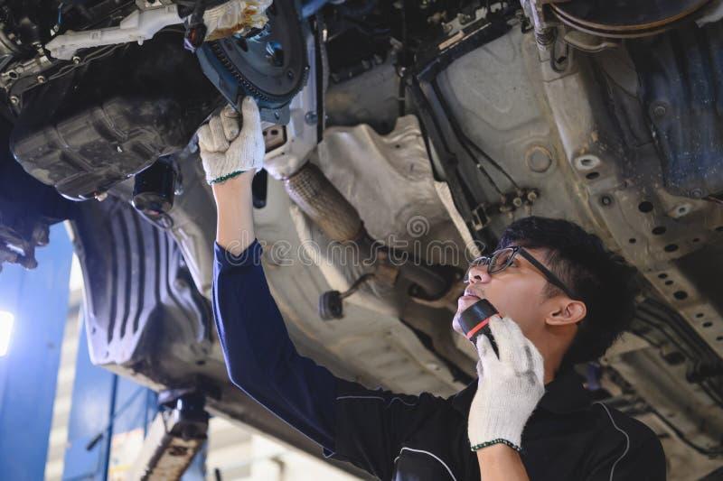 Aziatische mannetjes voor mechanisch handvat en knipperlicht voor het onderzoeken van auto's onder chassis van auto's Inspectie v royalty-vrije stock foto's