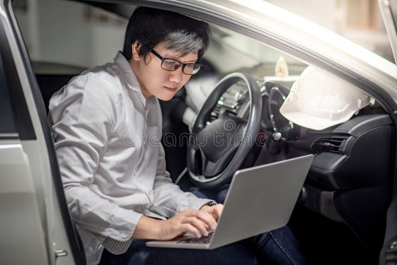 Aziatische mechanische ingenieur die met laptop in de auto werken stock fotografie