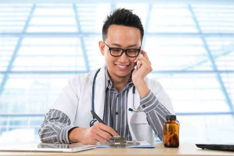 Aziatische medische arts die aan bureau werken stock foto's