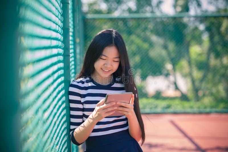 Aziatische meisje en computertablet in hand status met toothy smil stock foto's