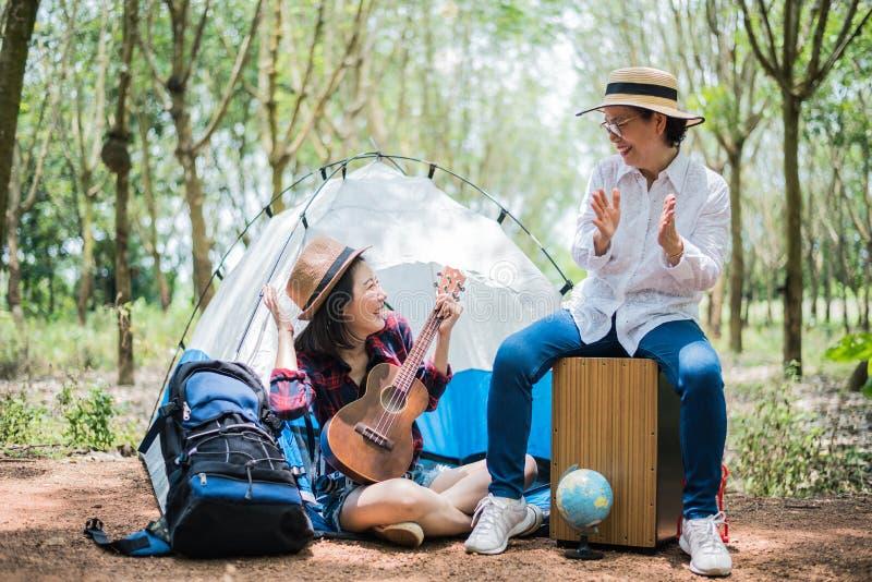 Aziatische meisje en moeder speelmuziek in in openlucht bosmensen en levensstijlenconcept Aard en reisthema stock foto