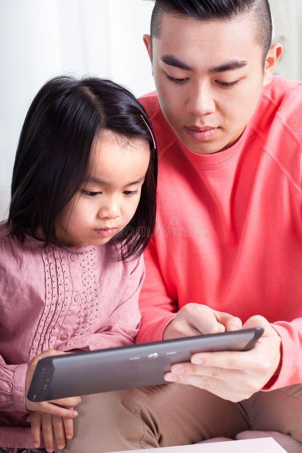 Aziatische meisje en papa die tablet gebruiken stock foto's