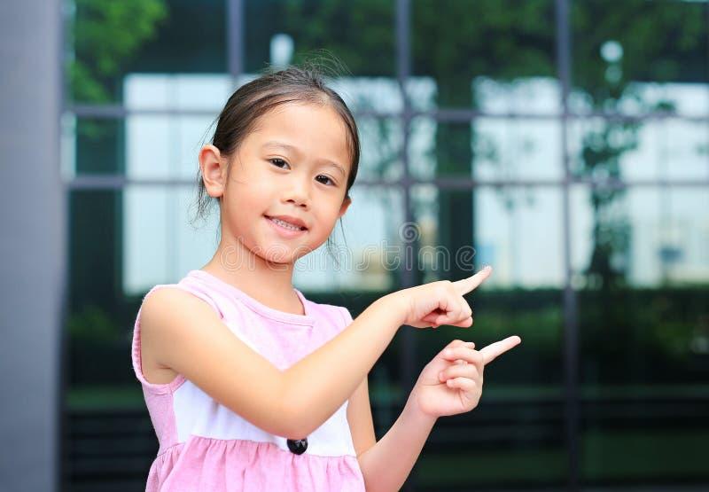 Aziatische meisjehouding die haar wijsvinger naast met leuke glimlach richten royalty-vrije stock afbeeldingen